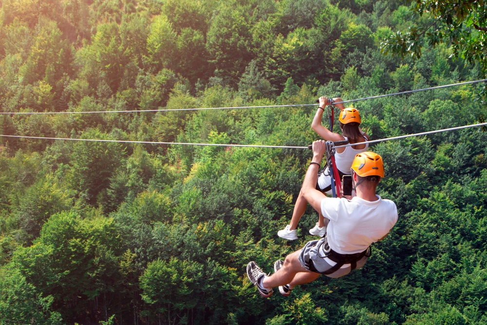 couple duel ziplining in the mountains